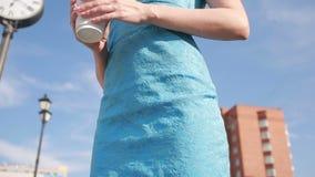Το κορίτσι στέκεται κοντά στο ρολόι και τον καφέ κατανάλωσης Αναμονή απόθεμα βίντεο
