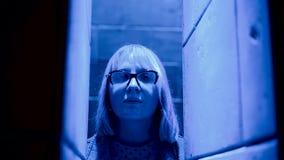 Το κορίτσι στέκεται μεταξύ των όμορφων στηλών με τον όμορφο ζωηρόχρωμο φωτισμό Δροσερό μήκος σε πόδηα απόθεμα βίντεο