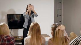 Το κορίτσι στέκεται μπροστά από το φίλο της στο σπίτι και το χορό, παρουσιάζοντας σκηνές για την εικασία, παιχνίδι συλλαβόγριφων απόθεμα βίντεο
