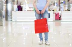το κορίτσι στέκεται στην αίθουσα της λεωφόρου στα τζιν με μια κόκκινη τσάντα αγορών στοκ εικόνες