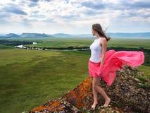 Το κορίτσι στέκεται στην κορυφή του βουνού, κοιτάζοντας έξω στην απόσταση στη φύση Στοκ Φωτογραφία
