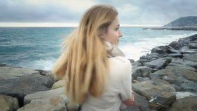 Το κορίτσι στέκεται στην παραλία κατά τη διάρκεια της θύελλας στη θάλασσα φιλμ μικρού μήκους