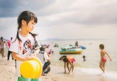 Το κορίτσι στέκεται στην πολυάσχολη παραλία κοιτάζοντας έξω στον ωκεανό Στοκ φωτογραφίες με δικαίωμα ελεύθερης χρήσης