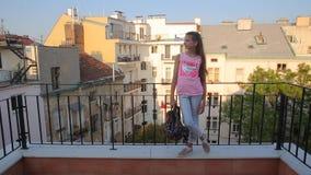 Το κορίτσι στέκεται στο μπαλκόνι και βγαίνει του πλαισίου απόθεμα βίντεο