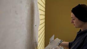 Το κορίτσι στα άσπρα γάντια βάζει έναν τοίχο μπροστά από την επισκευή Spatula, ασβεστοκονίαμα Ομαλοί τοίχοι φιλμ μικρού μήκους