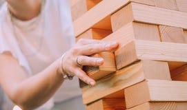 Το κορίτσι στα άσπρα ενδύματα με τα εξαρτήματα ο βραχίονάς της χτίζει το ξύλο πύργων στοκ εικόνα
