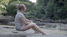 Το κορίτσι στα ακουστικά ακούει τη μουσική στη φύση Χαλαρώστε απόθεμα βίντεο