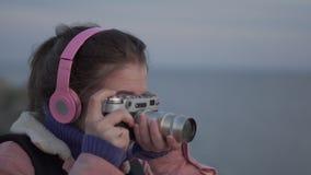 Το κορίτσι στα ακουστικά παίρνει μια εικόνα του ηλιοβασιλέματος θάλασσας στην εκλεκτής ποιότητας κάμερα της απόθεμα βίντεο