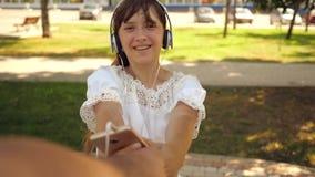 το κορίτσι στα ακουστικά χαμογελά και με το τηλέφωνο που χορεύει και που περιστρέφει με το αγαπημένο άτομό της η εκμετάλλευση παρ απόθεμα βίντεο