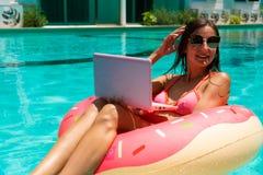 Το κορίτσι στα γυαλιά ηλίου κάθεται σε έναν διογκώσιμο κύκλο στη λίμνη με ένα ρόδινο lap-top στοκ φωτογραφίες με δικαίωμα ελεύθερης χρήσης