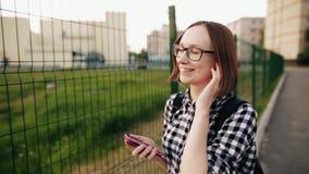 Το κορίτσι στα γυαλιά κυλά το κεφάλι της στο ρυθμό του αγαπημένου τραγουδιού της κίνηση αργή φιλμ μικρού μήκους