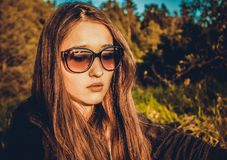 Το κορίτσι στα γυαλιά στο υπόβαθρο της φύσης στοκ φωτογραφίες