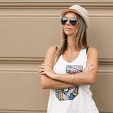 Το κορίτσι στα γυαλιά ηλίου και ένα καπέλο στέκεται κοντά στον τοίχο Στοκ Φωτογραφίες