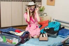 Το κορίτσι στα γυαλιά ηλίου και ένα καπέλο συσκευάζει μια βαλίτσα στις διακοπές Στοκ Εικόνες