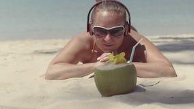 Το κορίτσι στα γυαλιά ηλίου και τα ακουστικά, που βρίσκονται στην άμμο κοντά στη θάλασσα και εξετάζει την καρύδα φιλμ μικρού μήκους