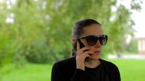 Το κορίτσι στα γυαλιά ηλίου τελειώνει τη συνομιλία στο τηλέφωνο και κλείνει το τηλέφωνο στο πράσινο πάρκο απόθεμα βίντεο