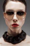 Το κορίτσι στα γυαλιά σε ένα μαύρο υπόβαθρο με τα κόκκινα χείλια Στοκ Εικόνες