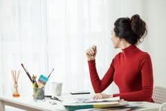 Το κορίτσι στα κόκκινα ενδύματα κάθεται στο γραφείο Άποψη παραθύρων Στοκ Εικόνα
