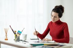 Το κορίτσι στα κόκκινα ενδύματα κάθεται στο γραφείο lifestyle Εργασιακός χώρος καλλιτεχνών ` s Στοκ Εικόνα