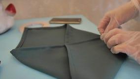 Το κορίτσι στα λαστιχένια γάντια διπλώνει ήπια μια πετσέτα στον πίνακα συμποσίου Προετοιμάζει τον πίνακα για το γεγονός απόθεμα βίντεο