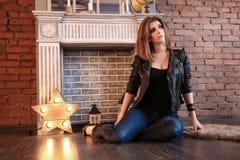 Το κορίτσι στα μαύρα σακάκια δέρματος που θέτουν τη συνεδρίαση στο πάτωμα Στοκ Φωτογραφίες