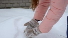 Το κορίτσι στα μπεζ γάντια κάνει ένα κομμάτι του χιονιού, τινάζει από το χιόνι, χειμερινές διακοπές, Χριστούγεννα και έννοια ανθρ φιλμ μικρού μήκους