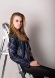 Το κορίτσι στα σορτς ενός δέρματος σακακιών δέρματος είναι βασισμένο σε ένα stepladder Στοκ Εικόνα