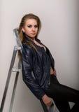 Το κορίτσι στα σορτς ενός δέρματος σακακιών δέρματος είναι βασισμένο σε ένα stepladder Στοκ Φωτογραφία