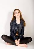 Το κορίτσι στα σορτς ενός δέρματος σακακιών δέρματος είναι βασισμένο σε ένα stepladder Στοκ εικόνα με δικαίωμα ελεύθερης χρήσης
