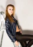 Το κορίτσι στα σορτς ενός δέρματος σακακιών δέρματος είναι βασισμένο σε ένα stepladder Στοκ φωτογραφία με δικαίωμα ελεύθερης χρήσης