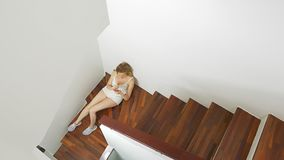 Το κορίτσι στα σορτς κάθεται στα σκαλοπάτια στο σπίτι και χρησιμοποιεί ένα smartphone απόθεμα βίντεο