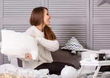 Το κορίτσι στα Χριστούγεννα κτυπά τα μαξιλάρια παίζοντας στο σπίτι Στοκ εικόνα με δικαίωμα ελεύθερης χρήσης