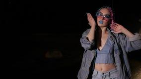 Το κορίτσι στα χρωματισμένα γυαλιά ηλίου χορεύει απόθεμα βίντεο