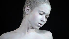 Το κορίτσι στην άσπρη τέχνη σωμάτων στέκεται με τις προσοχές της ιδιαίτερες και τα συνοφρυώματα φιλμ μικρού μήκους