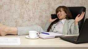 Το κορίτσι στην εργασία στην αρχή διαπραγματεύεται στο smartphone με το φλιτζάνι του καφέ διαθέσιμο Εργασία υπολογιστών Όμορφη επ απόθεμα βίντεο