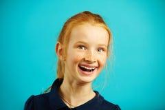 Το κορίτσι στην εύθυμη διάθεση με το φωτεινό πρόσωπο εξετάζει σας απομονωμένο στο μπλε υπόβαθρο, φορά τη juicy κόκκινη τρίχα, όμο στοκ φωτογραφία με δικαίωμα ελεύθερης χρήσης