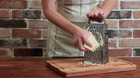 Το κορίτσι στην κουζίνα τρίβει το τυρί στον ξύστη απόθεμα βίντεο