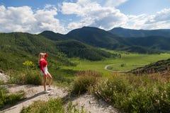 Το κορίτσι στην κόκκινη κορυφή και τα μπλε σορτς εξετάζει την απόσταση στην άκρη ενός απότομου βράχου στα βουνά Altai, είναι κατω στοκ φωτογραφία