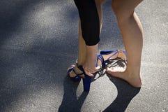 Το κορίτσι στην οδό βγάζει τα ανήσυχα σανδάλια της Στοκ Φωτογραφία