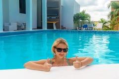 Το κορίτσι στην πισίνα παρουσιάζει αντίχειρες στοκ φωτογραφία