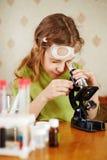 Το κορίτσι εξετάζει προσεκτικά το μικροσκόπιο στοκ φωτογραφία