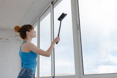 Το κορίτσι στην τυρκουάζ μπλούζα και τα μπλε σορτς πλένει το παράθυρο στοκ εικόνα με δικαίωμα ελεύθερης χρήσης