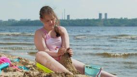 Το κορίτσι στηρίζεται ένα κάστρο άμμου στην όχθη ποταμού απόθεμα βίντεο