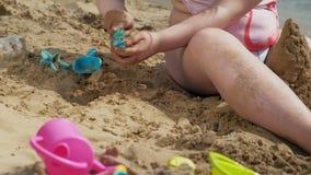 Το κορίτσι στηρίζεται ένα κάστρο άμμου στην όχθη ποταμού φιλμ μικρού μήκους