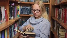Το κορίτσι στη βιβλιοθήκη επιλέγει τα βιβλία απόθεμα βίντεο