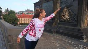 Το κορίτσι στη γέφυρα του Charles αγγίζει αποτυπωμένη σε ανάγλυφο pictur απόθεμα βίντεο