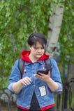 Το κορίτσι στη μπλε ζακέτα και το κόκκινο πουλόβερ στο υπόβαθρο των δέντρων εξετάζει το smartphone της στοκ εικόνες