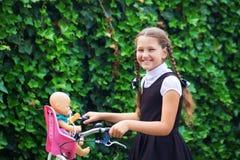 Το κορίτσι στη σχολική στολή οδηγά το ποδήλατο πίσω σχολείο Στοκ Φωτογραφία