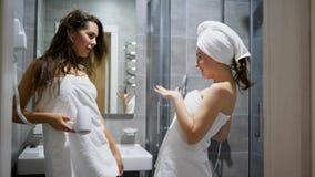 Το κορίτσι στις άσπρες πετσέτες τραγουδά στη χτένα και το χορό μπροστά από τον καθρέφτη φιλμ μικρού μήκους
