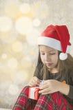 Το κορίτσι στις πυτζάμες με παρουσιάζει τα κιβώτια στο πρωί Χριστουγέννων Στοκ Φωτογραφία